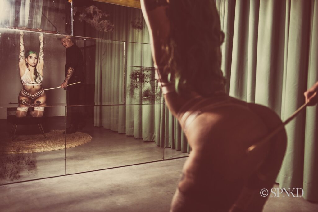 Woman standing in front of a mirror holding her hands up. Her lover is caning her.