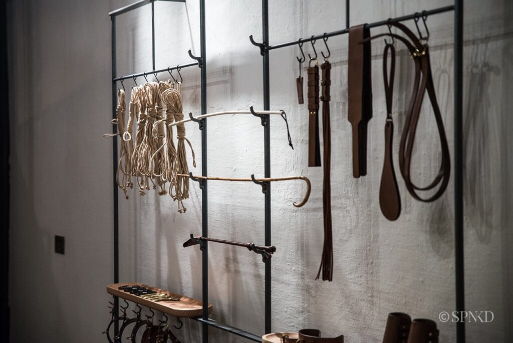 A metal display of BDSM tools and toys. Ropes, canes, and spanking tools.